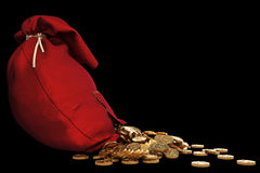 Bag. Pile of gold coins spill out of the red bag with a patch. with clipping path Royalty Free Stock Photography