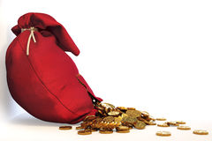 Bag. Pile of gold coins spill out of the red bag with a patch. with clipping path Stock Photo