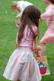 In the Bag. Young girl drops easter egg into her bag Royalty Free Stock Photo