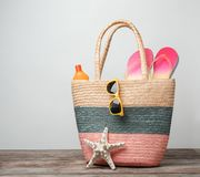 Bag with beach objects on table. Against light background stock image