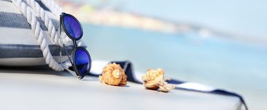 Bag on the beach with sunglasses, shells and towel. Bag on the beach with blue sunglasses, shells and towel royalty free stock photography