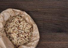 Bag with brown rice on wooden backgroung. Bag with raw brown wholegrain rice on wooden backgroung Royalty Free Stock Images