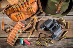 Bag with bullets, binoculars and hat in a hunting lodge Stock Photo