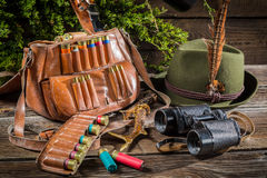 Bag with bullets, binoculars and hat in a hunting lodge Stock Images