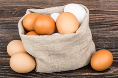 Bag of burlap with brown and white eggs on table Stock Image
