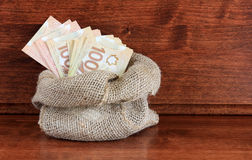 Bag of Canadian Cash. Burlap sack of Canadian one hundred and fifty dollar bills Stock Images