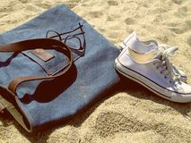 Bag and canvas shoes on beach