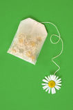 Bag of chamomile tea over green background Stock Images