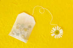 Bag of chamomile tea over yellow handmade paper Royalty Free Stock Photography