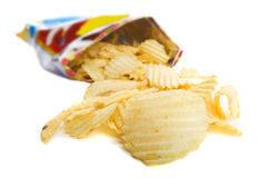 Bag of chips. Spilt bag of ripple chips on a white background royalty free stock image