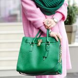 Bag close-up in female hands. Stylish modern and feminine image, style. Girl with a green bag in a pink coat