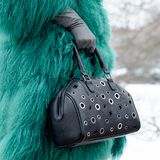 Bag close-up in female hands. Stylish modern and feminine image, style. Girl in a green coat with a black bag and gloves