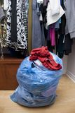 Bag of clothes in closet. Bag of clothes taken out of a closet, ready to be donated or given away royalty free stock image