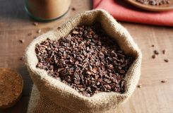 Bag with cocoa nibs. On wooden table stock images