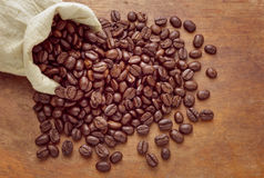 Bag of coffee beans on grunge wooden background. Royalty Free Stock Photography