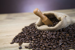 Bag of coffee beans on wooden table Royalty Free Stock Images