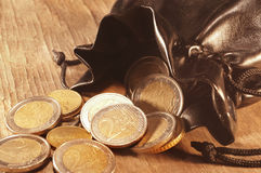 Bag of coins. On a beautiful textured table Royalty Free Stock Photo