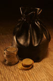 Bag of coins. On a beautiful textured table Stock Image