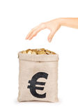 Bag of coins with hand Royalty Free Stock Image