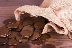 Bag of coins spilt over a wooden surface Stock Image