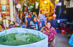 The bag with dried herb, Vakil Bazaar, Shiraz, Iran. SHIRAZ, IRAN - OCTOBER 14, 2017: The crowded alleyway of historical Vakil Bazaar with a view on the bag of stock photo