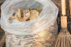 Bag of dry leaves with broom Royalty Free Stock Photo