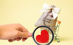 Bag with euro sign and red heart in a supermarket trolley. Charity. Donation. Social help. Volunteering. Saving money. royalty free stock photos