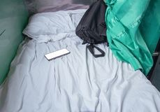 Bag fabric black and cell phone on white bed in Interior train with copy space add text.  Royalty Free Stock Image