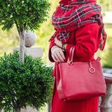 Bag in female hands. A girl in a red coat and a warm woolen scarf. Close-up. Gift vouchers, Black Friday, Cyber Monday, Boxing Day, casual, elegant, hipster Royalty Free Stock Photo