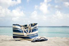 Bag and flip-flops on the beach Royalty Free Stock Photos