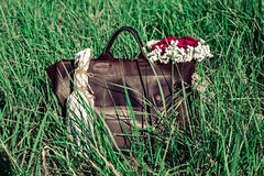 Bag and flowers. In green grass Stock Images