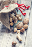 Bag full of nuts and almonds. On wood board royalty free stock photos