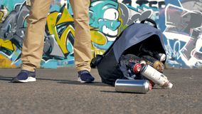A bag full of spray paint bottles falls down on pavement. A low view on an open backpack with spray paints falling down near someones legs stock footage