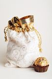 Bag for gifts. White and golden bag for gifts & golden sphere chocolate candy stays at white background Royalty Free Stock Images