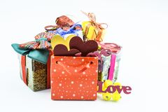Festive boxes of different colors and a red bag close-up on a white background. Bag with gifts in the form of colorful hearts and the words `love royalty free stock images
