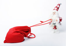 Bag With Gifts And Santa. Santa claus pulls a bag with presents isoleted on white Stock Photography