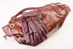Bag, glasses and gloves. Stylish red female handbag, glasses and gloves on a white background stock image