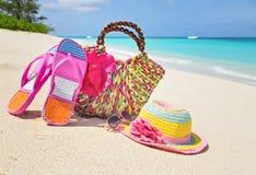Bag, hat, flip-flops and sunglasses on sunny beach, tropical bea Stock Photos