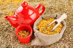 Bag with healing herbs and red tea kettle Stock Photography