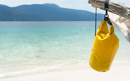 Bag hung on the timber against beach background. Stock Image