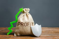 Bag with the inscription Profit, green up arrow and silver shield. concept of growth and protection of investments and income. Guarantee of deposits. Reducing stock images