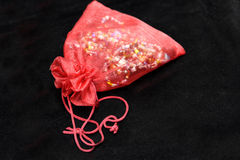 Bag for jewelry. Red bag for jewelry storage on black background Royalty Free Stock Images