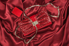 Bag of lacquered leather and red perfume lying on red silk. Handbag for women and bottle of scent, top view. Royalty Free Stock Image
