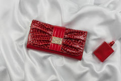 Bag of lacquered leather and red perfume lying on white silk. Handbag for women and bottle of scent, top view. Stock Photos