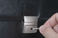 Bag lock with key and hand Royalty Free Stock Photo