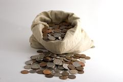 Bag of money. Coins spilling out of a bag Royalty Free Stock Photography