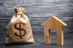 A bag with money and a House with a large doorway. Concept of real estate acquisition and investment. Affordable cheap loan stock image