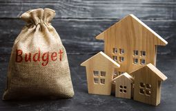 Bag with money and the inscription Budget and wooden houses. The concept of the city budget. Financing in the country. Investing stock photos