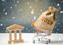A bag of money with the inscription 2019 in a supermarket trolley stands near the bank. Adoption of the budget 2019. Payment of stock photo