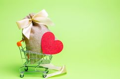 Bag with money and red heart. Valentine`s Day. Saving money. Accumulation. Buying gifts to your loved one. Preparation for the stock photos